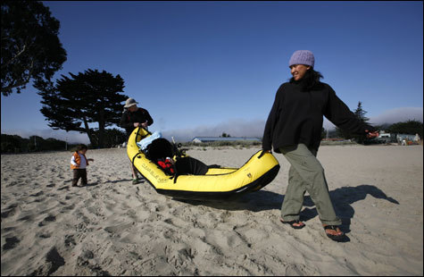 Leah and Gabe Boyd, of Morgan Hill, Calif., walk their kayak to the ocean with their daughter Lucy in Monterey.