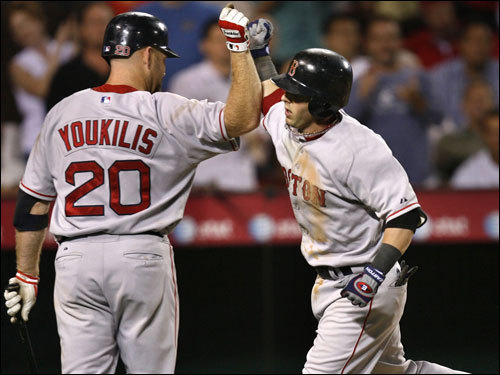 Pedroia (right, receiving congratulations from Youkilis) led off the seventh with a solo home run to put the Red Sox on top, 7-6. Boston added two more runs in the eighth to pad its lead.