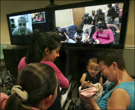 Deployed to Iraq in March, Lance Corporal Tyrelle Greene, 22, watched via two-way video Monday night as his 7-pound, 12-ounce daughter Janelle was born. Greene (far left) observed as his brother Antonio Gardner, 3, reached out to touch Janelle Margaret as his aunt Laura held the baby. At left, Greene's wife, Melissa.
