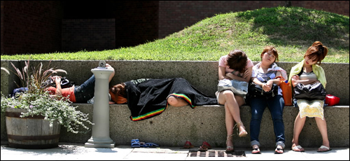 The warmth of the sun that finally broke through the day's haze was just enough to coax this between-classes nap Tuesday at the UMass-Boston campus. Students from Japan are studying American Language and Culture in a short summer program. They are: (from left) Nami Yoshida, 19, Misaki Mizuno, 19, Ai Mizutani, 20, Keiko Suzuki, 20, and Risa Suzuki, 19.