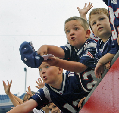 Some young fans were trying to get the attention of people who were tossing T-shirts into the crowd before the start of the Patriots' workout.