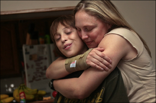 Sergeant Rebekah Spencer, right, embraced her son, Adam Engroff, 13, a few days before leaving for Fort Bragg to wait an eventual deployment to Iraq. Spencer's sister, Elizabeth Flagg, will raise Spencer's two children when she is gone.