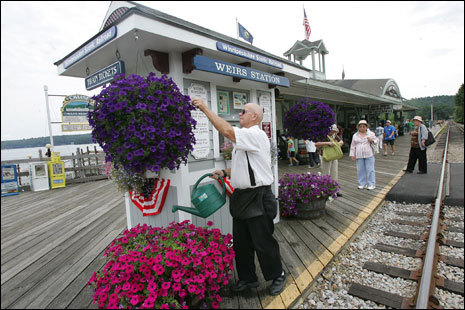 Station agent Dick Perley tends to the flowers at the ticket counter for the Winnipesaukee Scenic Railroad at Weirs Beach.