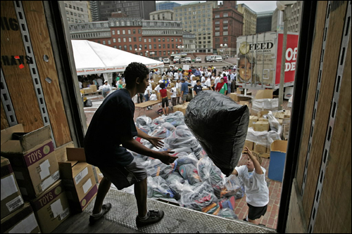 Richie Bembery of Jamaica Plain caught a bag of fully packed backpacks thrown up by Johnathan Maragnano of Plypmton. Volunteers packed with school supplies about 10,000 backpacks provided by Office Depot Foundation in partnership with Feed The Children for youngsters in need, at Boston City Hall Plaza.