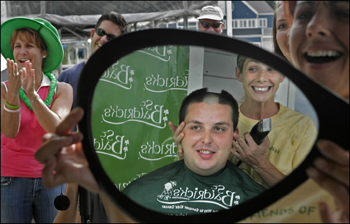 Kristen Doran of Harmony Cutz shaved the head of Quincy Firefighter William Eastwood Thursday as part of the St. Baldrick's Foundation's fund-raiser for children's cancer research. Doran's and Eastwood's images were reflected in a mirror held by Denyce Bobbitt. For the fund-raiser, firefighters and police officers solicit donations and then have their heads shaved.