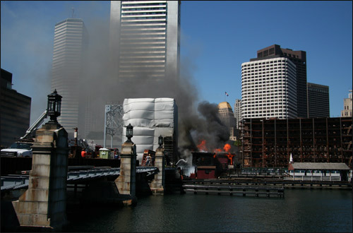 Flames and smoke billowed high into the clear blue sky as the Federal Reserve Bank building loomed in the background. The museum commemorates the events of Dec. 17, 1773, when a group of revolutionaries raided three ships at Griffin's Wharf. The men, disguised as Mohawk Indians, dumped 342 crates of British tea into Boston Harbor to protest a tax.