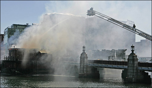As firefighting efforts intensified, the combination of fire and water sent plumes of smoke into the air.
