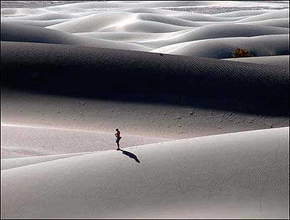 A lone hiker makes his way over the dunes.