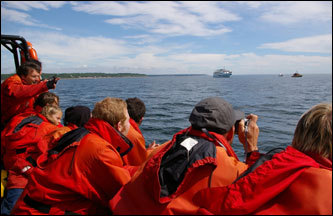 Passengers aboard a Zodiac in the St. Lawrence spot a whale in the distance.