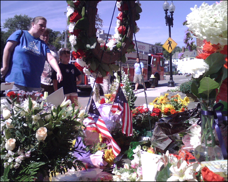 The memorial of wreaths, flowers, and American flags was built on the benches outside the station where firefighters often sit.