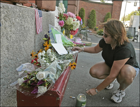 Karen Dolan left a candle in front of the West Roxbury firehouse on Centre Street Thursday.