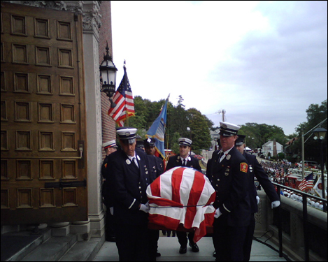 Cahill's casket was wrapped in an American flag as firefighters carried it into the Holy Name Church in West Roxbury.