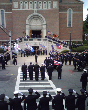 A firefighter carrying Cahill's helmet led the casket into the church.
