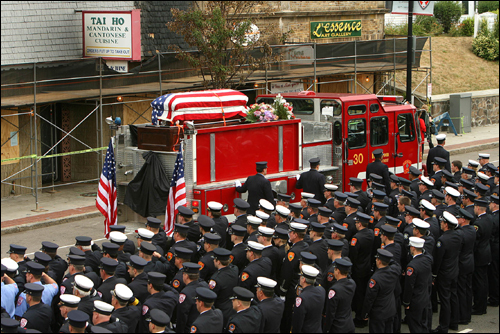 The casket of Paul J. Cahill was wrapped in an American flag on top of Engine 30 as the truck rolled slowly down Centre Street. The first of two firefighter funerals gripped West Roxbury today, as thousands lined the street in mourning. Cahill and Warren J. Payne died last week fighting a fire at a Chinese restaurant.