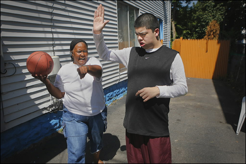 Dalene Basden coached 15-year-old Bryan Orozco in basketball at home. Basden earns 'time dollars' for watching the autistic teen. Taking literally the adage about time being money, Lynn Time Bank creates a circle of giving and receiving that is as much about fostering community as exchanging services.