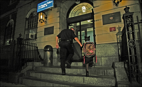 A Boston police officer escorted a 5-year-old child into the Area A1 police station Monday evening. The child, who was missing for several hours, was found in a Charlestown bus yard after having boarded the wrong bus after school.