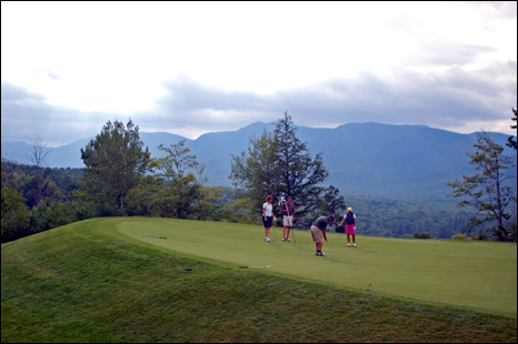 A foursome putts out on the severely sloped green on the par-4 third hole at Sunday River Golf Club.