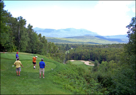 Players tee off on the par-3 11th hole at Sugarloaf Golf Club in Carrabassett Valley, Maine. The tee is 128 feet above the green and has views of the Bigelow Mountains.
