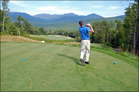 Assistant pro Peter Flint follows through on a tee shot at the Sunday River Golf Club in Newry, Maine. The course has expansive views of the Mahoosuc Mountains.