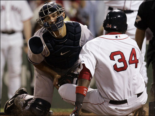 David Ortiz (right) was tagged out at the plate by Yankees catcher Jorge Posada (left), momentarily holding the Red Sox lead at 1-0. The Sox would later add a run in the inning.