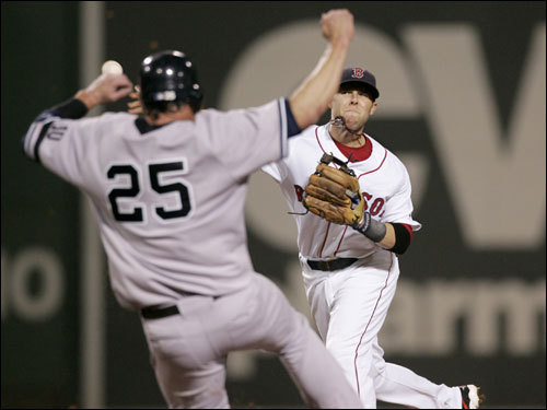Red Sox second baseman Dustin Pedroia (right) started a doubleplay in the first inning by tagging second base to retire Jason Giambi (left) and firing to first base.