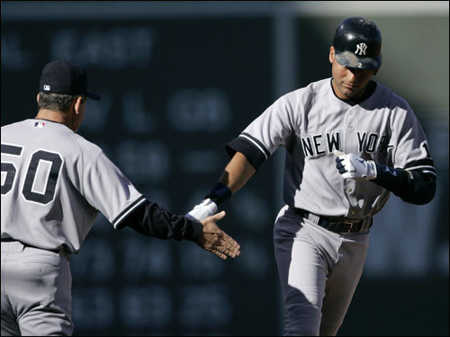 Yankees third base coach Larry Bowa (left) congratulated Derek Jeter (right) on his solo home run as he rounded third base.