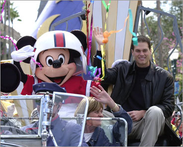 Super Bowl XXXVI most valuable player Tom Brady, Mickey Mouse, and Brady's mother, Galynn Brady, (center) rode through falling streamers in a parade at Disney's MGM Studios in Florida after Brady led the New England Patriots to an upset victory over the St. Louis Rams in Brady's first year as a starter.