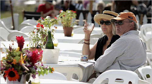 Wayne and Suzanne Franklin of Tiverton, R.I., sip champagne before the Newport International Polo Series match at Glen Farm Equestrian Center in Portsmouth.