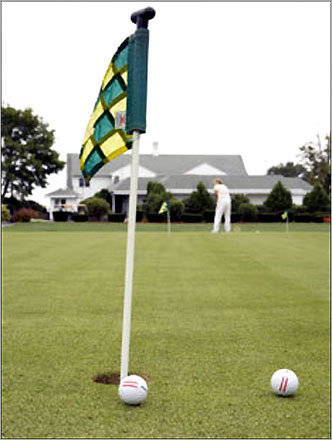 Golf balls sit on a putting green at the Green Valley Country Club.