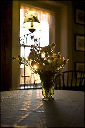 A floral arrangement glows in the evening sun of the main house of Shamrock Farm Inn Bed & Breakfast. Innkeeper William Conheeny serves a full Irish breakfast and hosts a happy hour overlooking the inn's gardens and a pond.