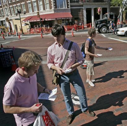 Harvard students Adam Goldenberg (in back) and Jon Staff (center) handed out fliers in Harvard Square yesterday protesting the Harvard Coop's policy preventing students from copying book identification numbers.