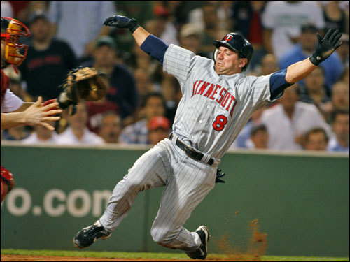Twins' Nick Punto (right) slid in and scored as Jason Varitek (left)waited for the late throw on a fifth inning single from Torii Hunter (not pictured).