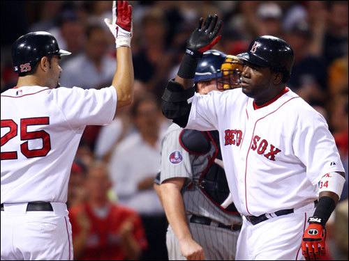 Red Sox third baseman Mike Lowell (25) celebrated with David Ortiz at home plate.