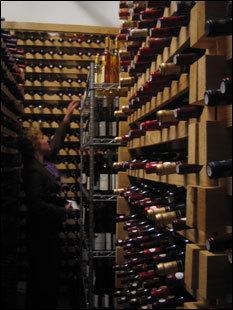 Sommelier Emily Wines pulls bottles from the cellar of the Fifth Floor Restaurant.