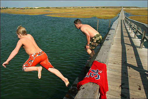 Brian Bondarek (right) from Sandwich brought his son Daniel, 10, to the boardwalk at Sandwich Beach where they enjoyed the warm temperature and jumped in the water at high tide.