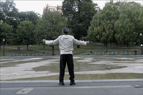 Early in the morning, a man performs calisthenics along the side of the empty Frog Pond.
