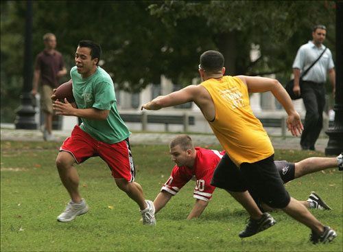Tufts University student Peter Evangelista ran with the ball and evaded the tag of Suffolk University student Tony Nardolillo (in red on the ground) during a tag football game on the Common.