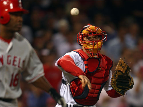Red Sox catcher Jason Varitek (right) threw to first base after dropping the third strike on Garrett Anderson (left).