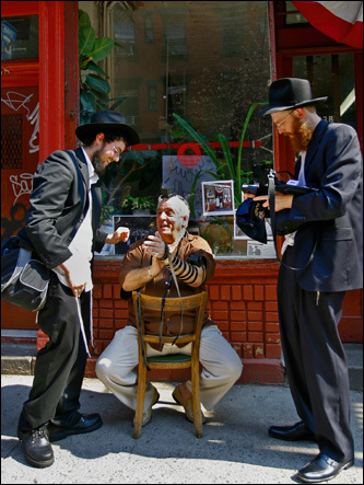 Asaf Advocat, left, Vinny Vella Sr., center, and Yosef Mandelbaum are filmed for a promo of a reality show outside Albanese Meat Market on Elizabeth Street. The butcher shop looks much like it must have when it opened in 1924. Martin Scorsese, who grew up on the block, filmed a scene here for his first movie, ''Who's That Knocking at My Door.''