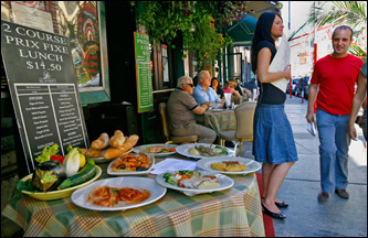 Samples of Italian specialties are displayed on a table outside Sal Anthony's S.P.Q.R. on Mulberry Street.