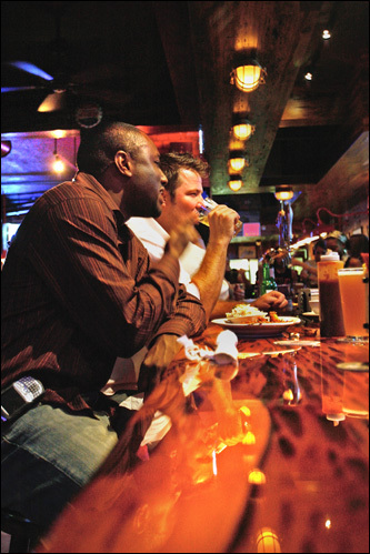 Clarence Faison, left, and Thomas Burns enjoy beers and a pulled pork sandwich.