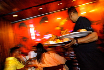 A waiter at Southern Hospitality delivers fried chicken to diners.