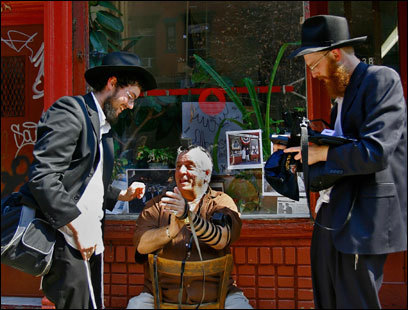Asaf Advocat (left), Yosef Mandelbaum (right), and actor Vinny Vella outside Albanese Meats and Poultry.