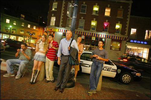 Regulars and passers-by stop in front of Cardullo's in Harvard Square to watch a Red Sox game on a TV in the window.