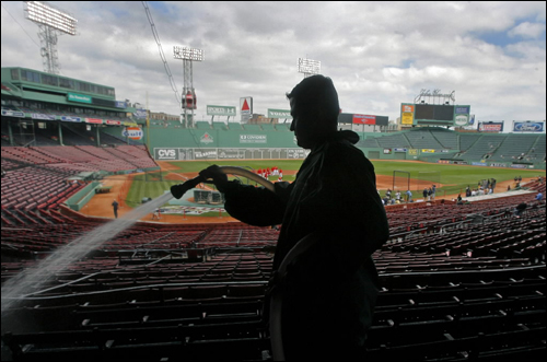 Before the Red Sox' first game in the 2007 American League Division Series at Fenway Park, Jose Aponte, from Aramark, was hosing down the stands, helping to get the park ready, while the Red Sox worked out on the field.
