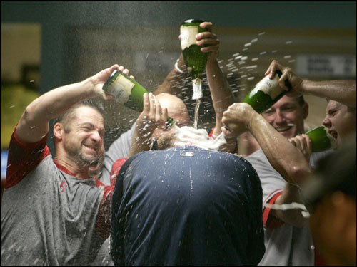 Members of the Red Sox pour champagne over the head of Schilling during the celebration.