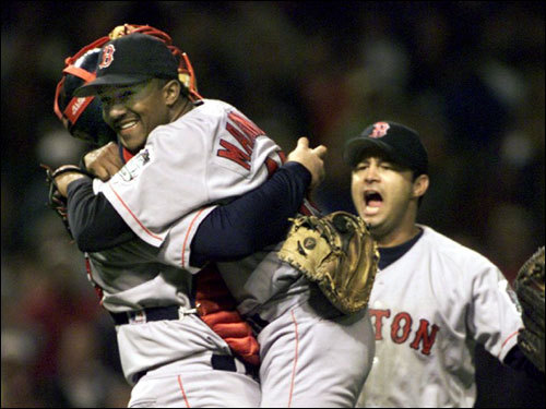Red Sox pitcher Pedro Martinez was hoisted by catcher Jason Varitek as John Valentin joined the celebration on the mound following the Red Sox victory over Cleveland in Game 5.
