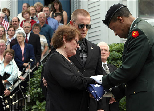 At the funeral service for Army National Guard Specialist Ciara Durkin at Saint John the Baptist Church, her mother, Angela Durkin is presented the flag that covered her casket by Major General Joe Carter of the Massachusetts National Guard. Her son Pierce stands with her.