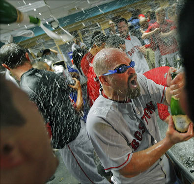 Champagne was flowing in the clubhouse after the Red Sox swept the Angels to advance to the ALCS. Here Kevin Youkilis dons protective goggles as he is sprayed at the same time he is looking for a victim.