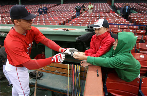 J.D. Drew (left) signed a baseball for fans before the game.